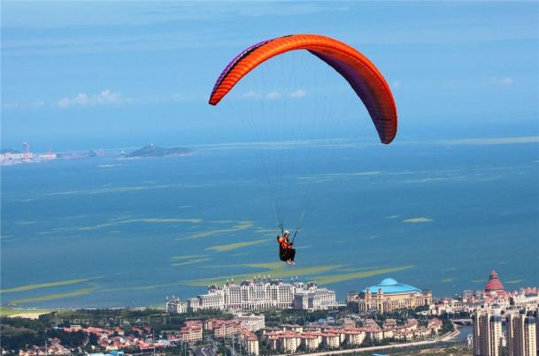 A person parasailing on a parachute  Description automatically generated with low confidence